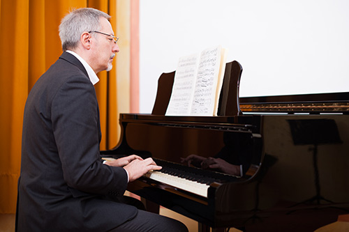 Man learning to play classical piano